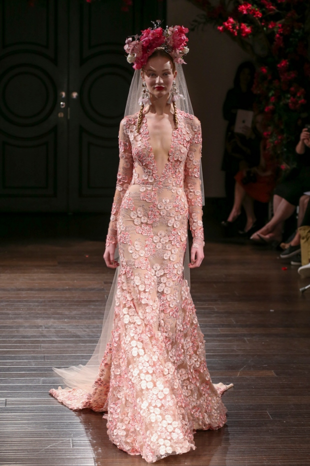 Vestido de encaje rosa con adornos de pedrería y manga larga. Pink floral lace wedding dress with beading and long sleeves.